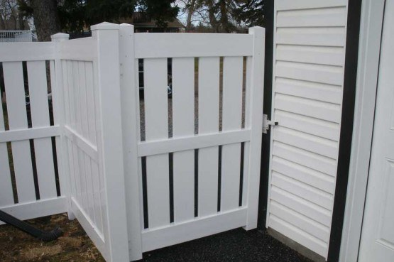 white semi private vinyl fence attached to home