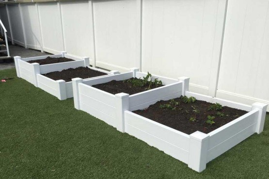four white planters on lawn filled with soil sitting in front of vinyl fencing