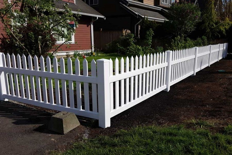 vinyl picket fence surrounding residential home backyard