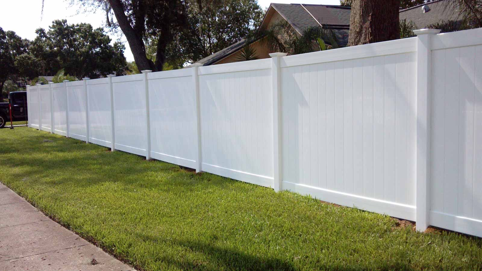 white vinyl privacy fence in front of home