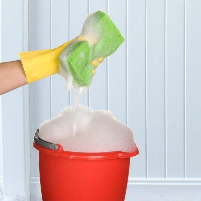 hand wearing yellow rubber glove holding green sponge above red bucket filled with bubbles