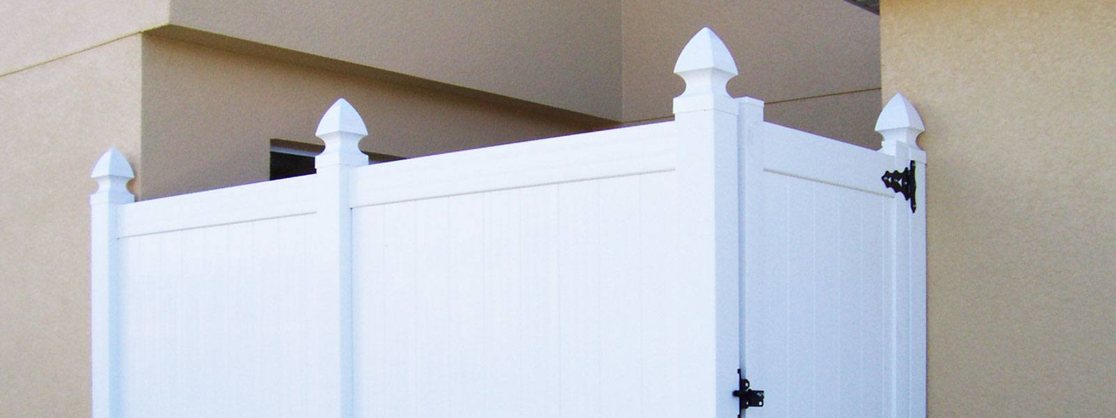 white vinyl fencing with decorative top pieces on each pillar