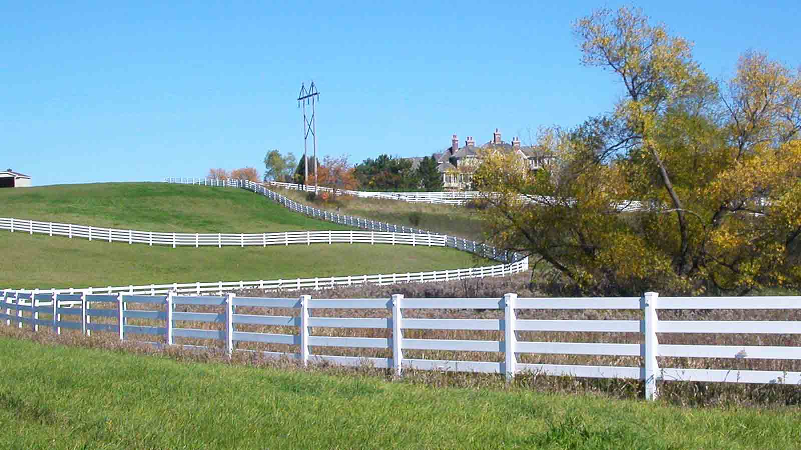 wide shot of large property lawn with four rail vinyl fence throughout and home in the distance