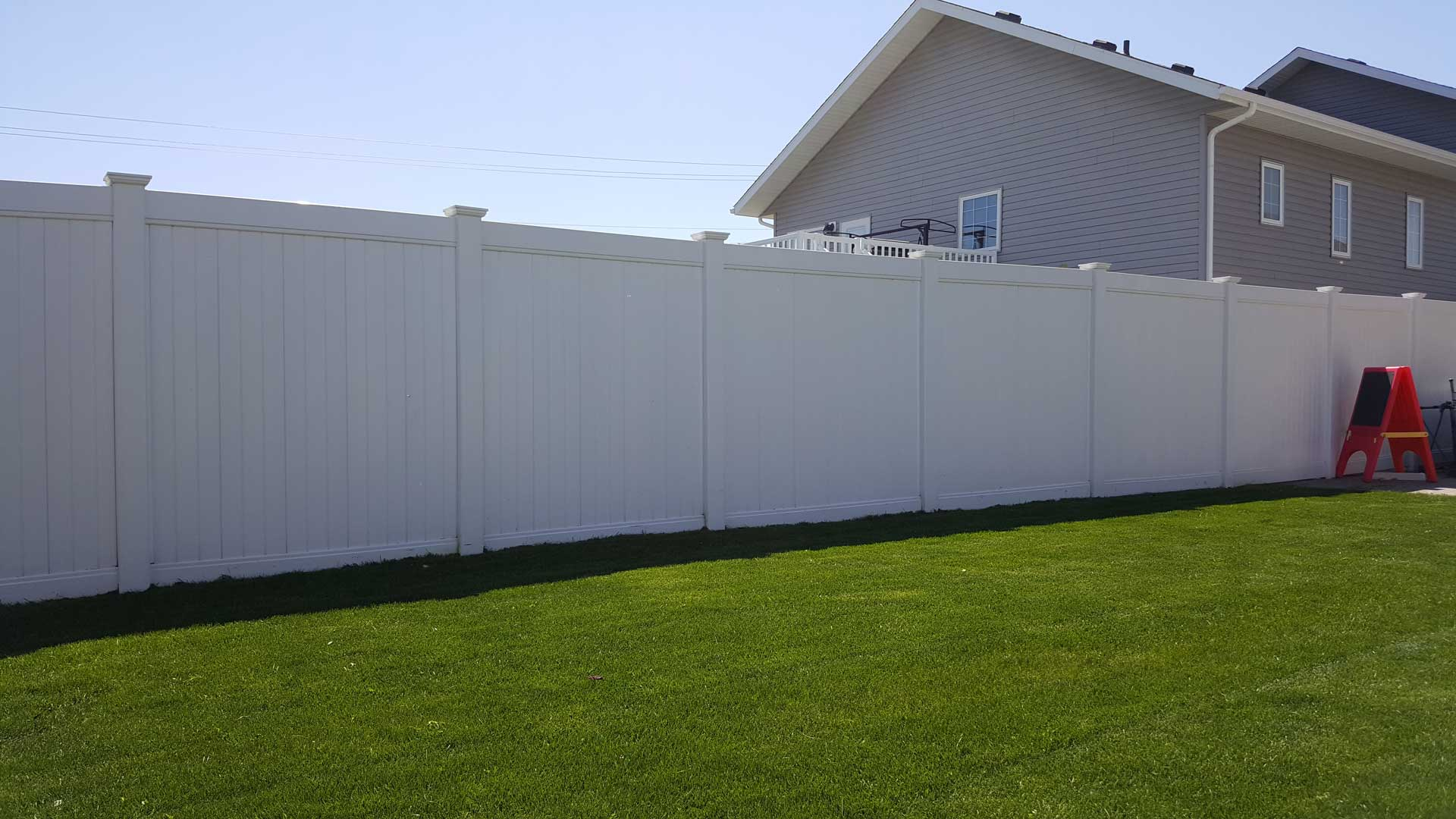 tall pvc vinyl privacy fence in backyard