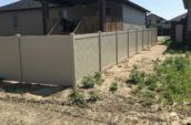 under construction area with home surrounded by pvc privacy final fence