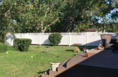 home backyard with large deck surrounded by pvc vinyl privacy fence