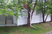 huron semi-privacy vinyl fence gate on the side of home beneath trees