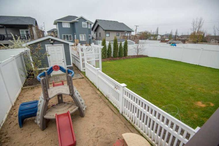 kinsmen vinyl picket fence enclosing shed and play area in home backyard