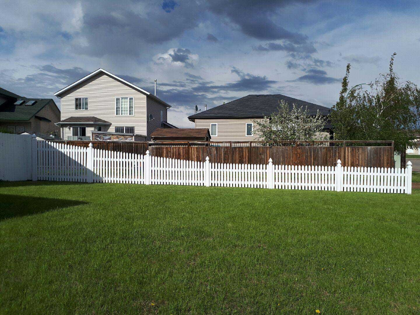 rising vinyl picket fence around home backyard