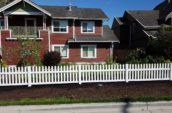 short vinyl picket fence surrounding backyard of home