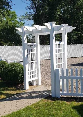 vinyl fence accessories entrance above stone pathway