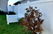 A newly installed white vinyl fence in a lush green backyard